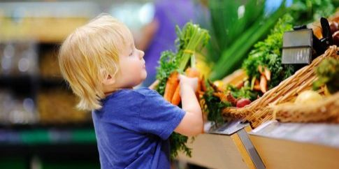 Cute-toddler-boy-in-supermarket-choosing-fresh-organic-carrots
