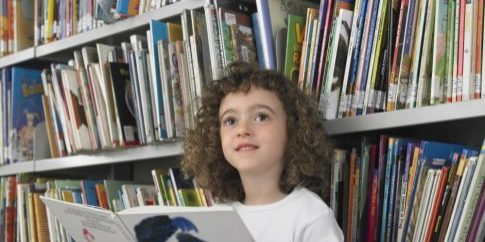 cute-little-girl-reading-storybook-in-library