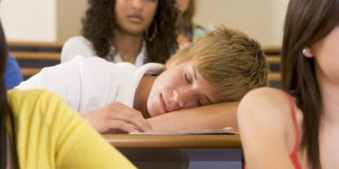 male-college-student-sleeping-through-a-university-lecture